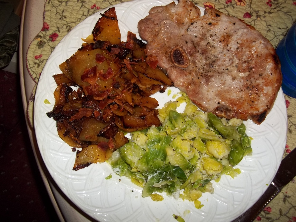 Fried rutabaga with broiled pork chop and Brussells sprout slaw
